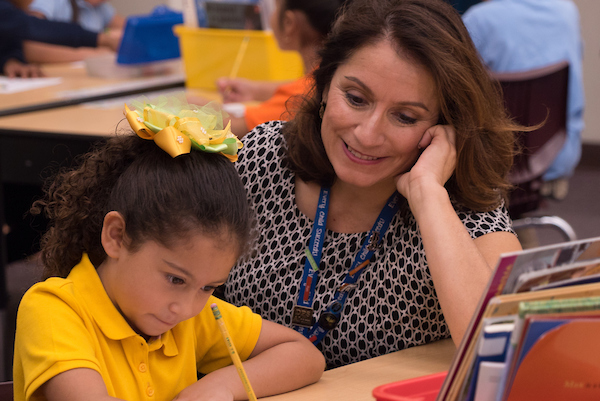 Superintendent Susana Cordova sits with a young student doing classwork