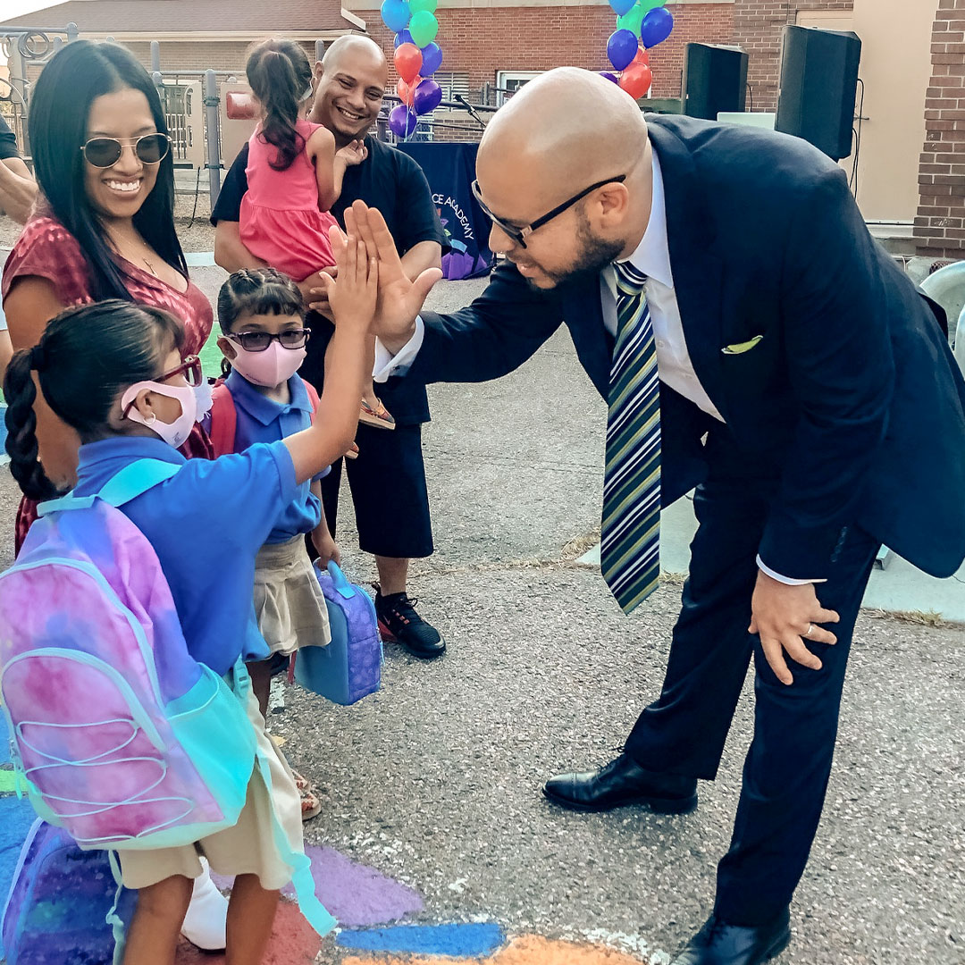 Dr. Marrero gives a student a high five on the first day of school near smiling parents at Garden Place Academy.