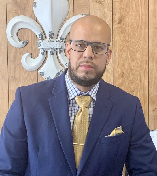 Dr. Alex Marrero looks at the camera in a navy suit, gold tie, and glasses.