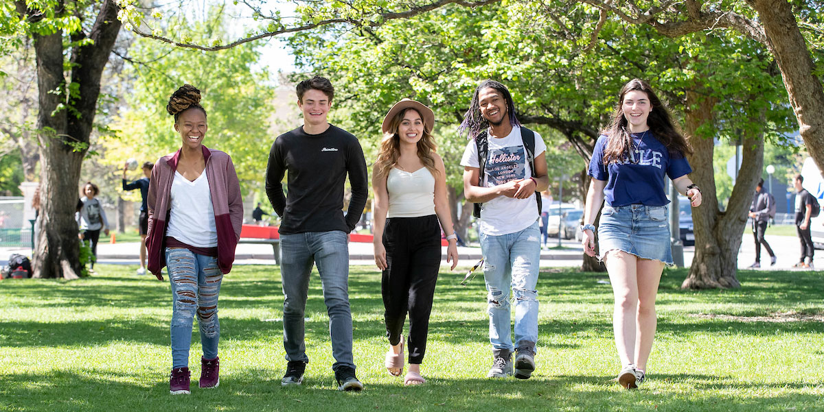 Five DPS students walk across a field.