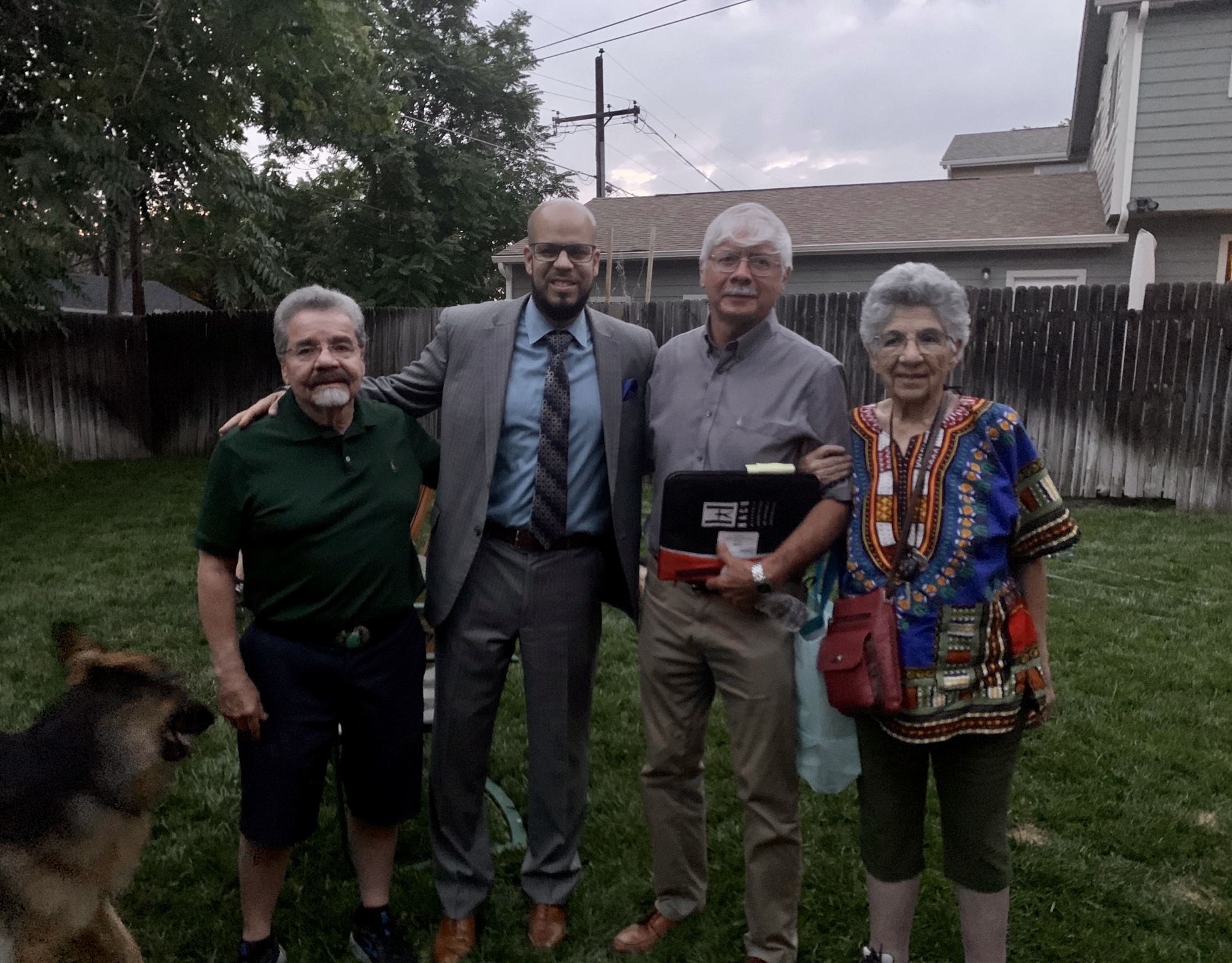 Dr. Alex Marrero poses with three community members in a backyard setting