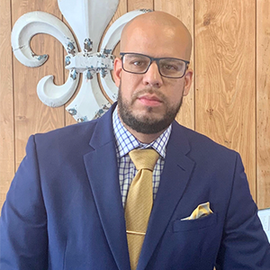 Dr. Alex Marrero wears glasses, a navy suit with a yellow tie, looking at the camera.