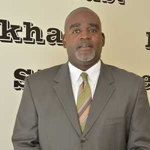 Andre Wright, wearing a dark tan suit and striped tie, looking at the camera.